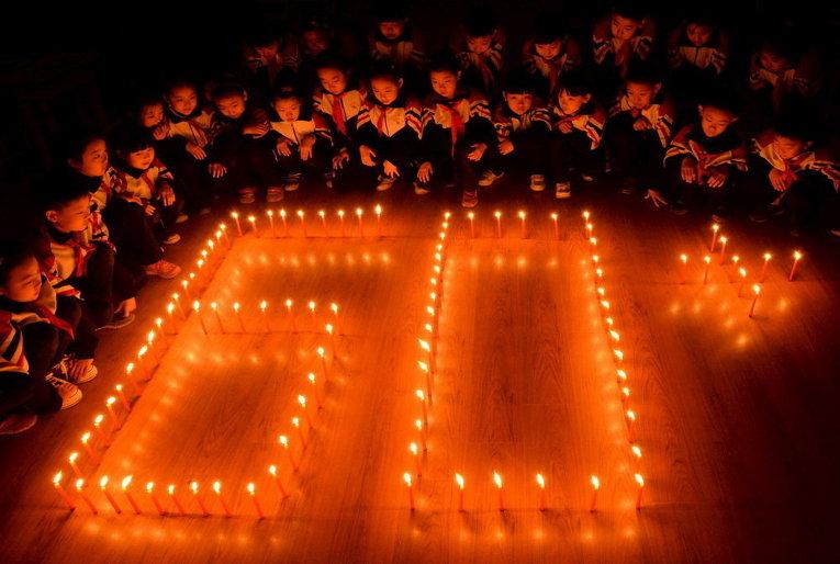 Ученики расставили свечи в форме логотипа Час Земли в начальной школе в китайском городе Ханьдань провинции Хэбэй
