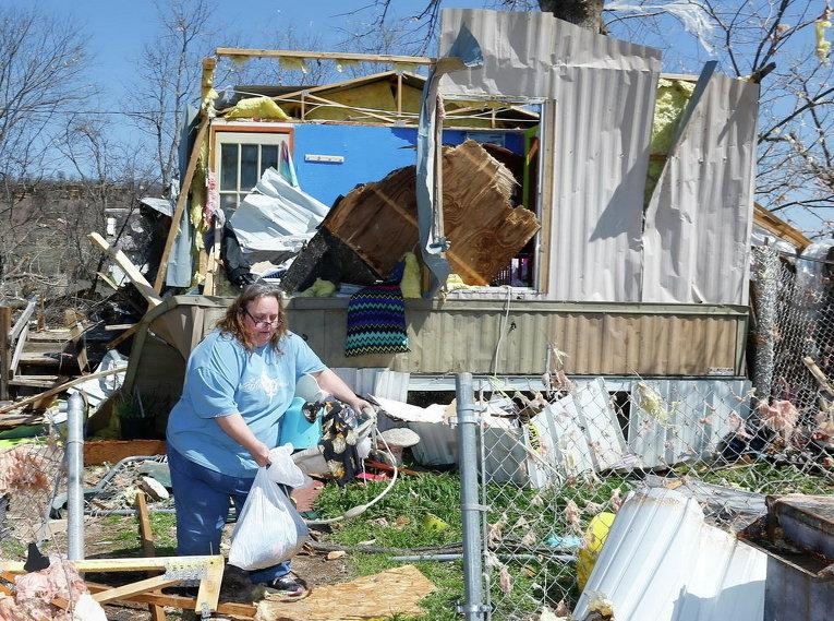 Женщина на фоне своего разрушенного торнадо дома на колесах в штате Оклахома