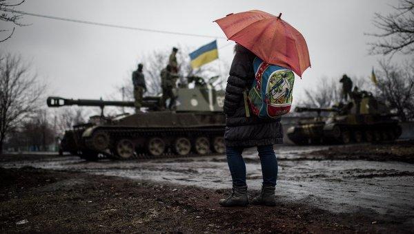 Школьница смотрит на технику украинских военных на окраине Донецка (4 марта 2015 года)