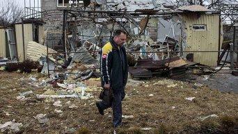Мужчина проходит мимо разрушенного в результате обстрела дома в жилом районе Донецка (5 марта 2015 года)