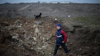 Мальчик стоит в воронке от взрыва в селе Чермалык на востоке Украины 26 февраля 2015 г