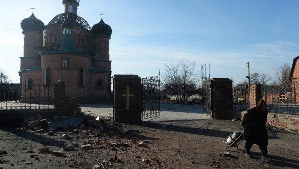 Женщина везет тележку с углем в поселке Октябрьский рядом с аэропортом Донецка