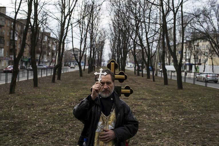 Православный священник во время поминовения жертв среди гражданского населения, погибших при обстреле в Донецке