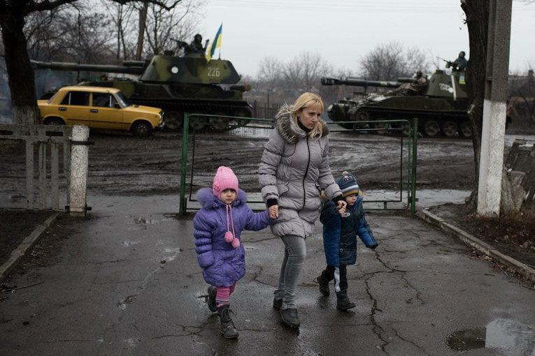 Местная жительница ведет детей в садик в Донецке