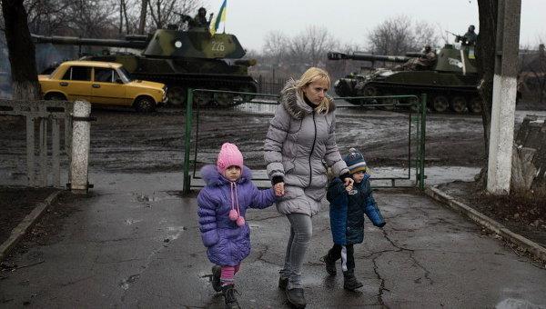 Местная жительница ведет детей в садик в Донецке, 4 марта 2015 г