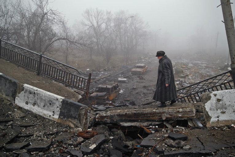 Женщина на разрушенном мосту близ аэропорта в Донецке
