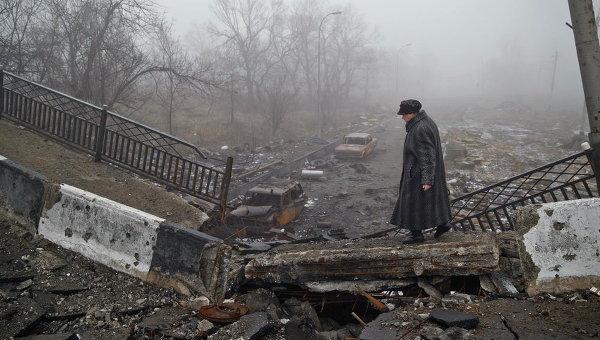 Женщина на разрушенном мосту близ аэропорта в Донецке. Архивное фото