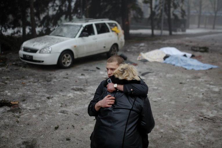 Мужчина успокаивает жену убитого местного жителя при обстреле в Донецке, 30 января 2015 г