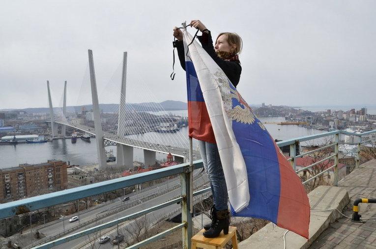 Женщина во Владивостоке привязывает траурную черную ленту в память о погибших с траулера Дальний Восток