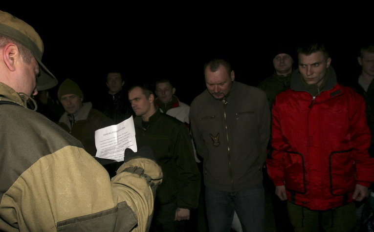 Ополченец читает список пленных военных, которые передаются украинской стороне в поселке Марьинка в Донецкой области