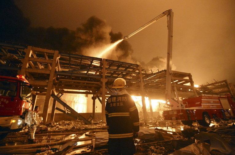 Пожарный наблюдает, как его коллеги пытаются потушить пожар на нефтехимическом заводе в Чжанчжоу