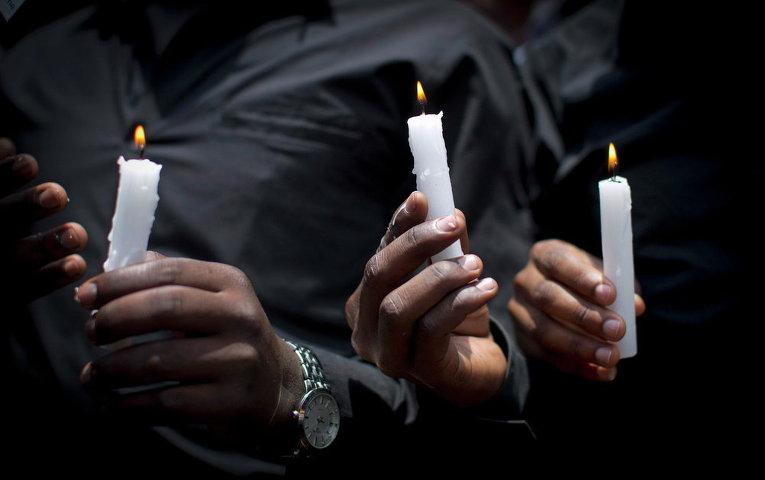 Кенийские студенты в черных одеждах и со свечами в память о погибших при теракте в колледже