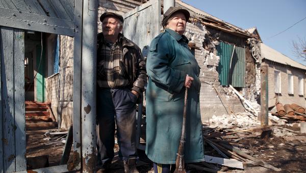 Пожилая пара смотрит на разрушения у своего дома в Дебальцево (9 марта 2015 года)