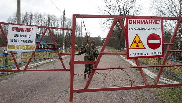 Сотрудник закрывает ворота на входе в зону отчуждения вокруг Чернобыльской АЭС, 21 апреля 2015