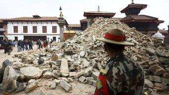 Непальский военнослужащий стоит перед разрушенным храмом