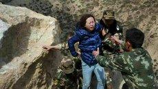 Спасатели помогают женщине добраться до безопасной зоны после оползня