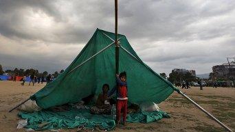 Непальская семья в импровизированном укрытии на открытой местности после землетрясения в Катманду