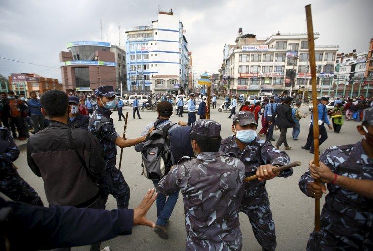 Непальские полицейские пытаются остановить жертв землетрясения от блокирования трафика на дороге