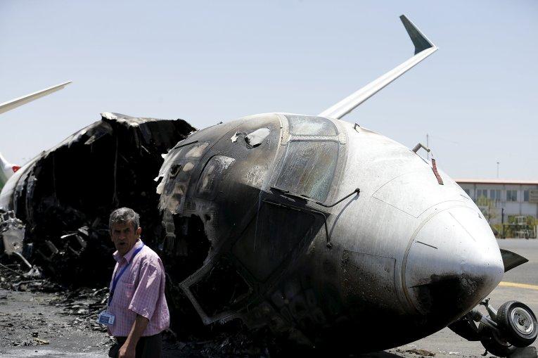 Представитель аэропорта проходит мимо самолета, разрушенного в результате авиаудара в Йемене