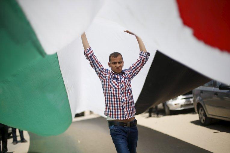 Палестинец с палестинским флагом во время демонстрации