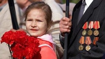 Девочка с гвоздиками возле ветерана. Архивное фото