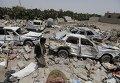 Мужчина идет на месте развалин в районе аэропорта Саны в Йемене