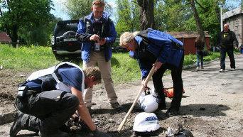 Сотрудники миссии ОБСЕ у дома, разрушенного в результате обстрела в Донецке.