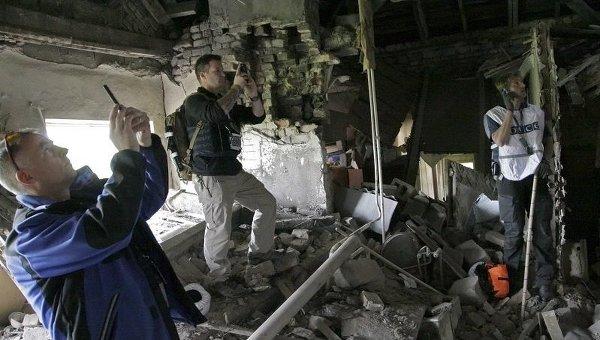 Наблюдатели ОБСЕ в Донецке фотографируют дом, разрушенный при обстреле