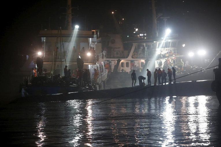 Спасатели на вершине затонувшего корабля на реке Янцзы, провинция Хубэй, Китай