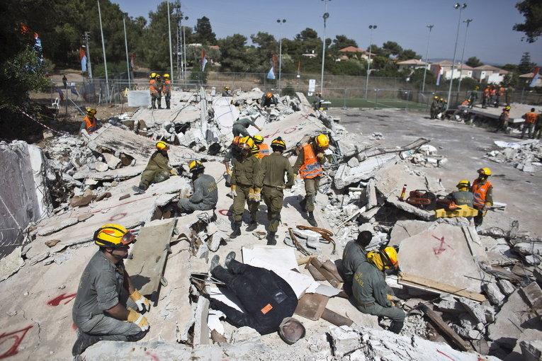 Израильские солдаты на обломках разрушенного здания на севере Израиля