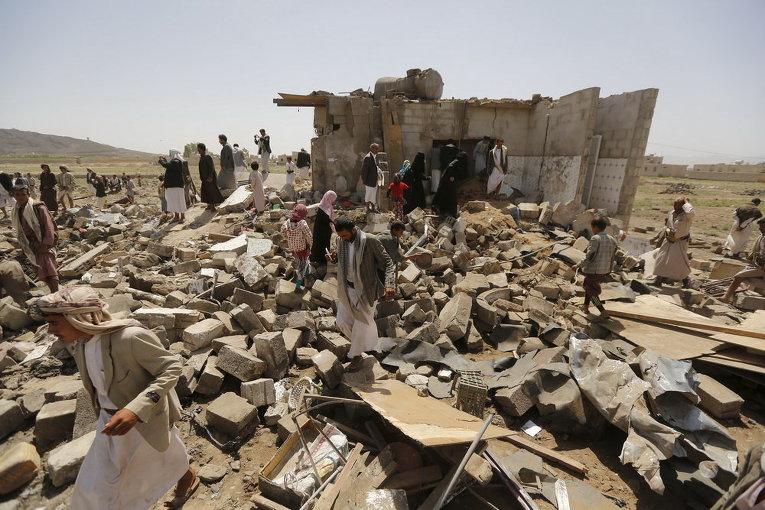 Йеменцы на развалинах домов, разрушенных авиаударами Саудовской Аравии