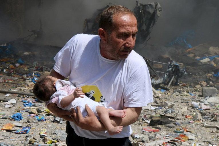 Мужчина с ребенком после удара бомбы в старом городе Алеппо