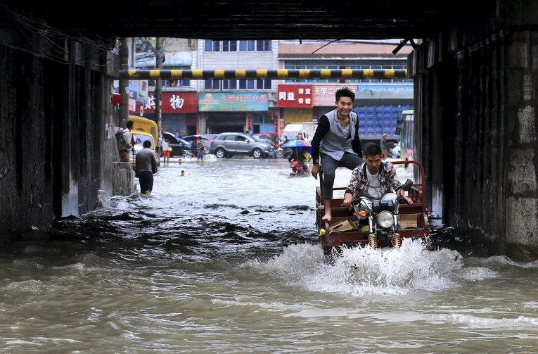 Мужчины едут по затопленной улице под мостом после проливных дождей в Аньшунь, провинция Гуйчжоу, Китай