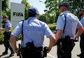 Швейцарские полицейские стоят перед входом в штаб-квартиру ФИФА в Цюрихе