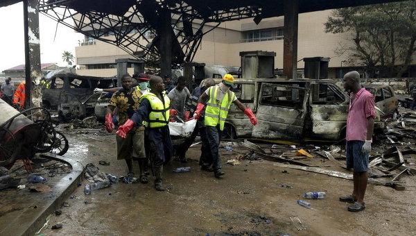 Спасатели несут труп с автозаправочной станции, которая взорвалась ночью в Аккре, Гана