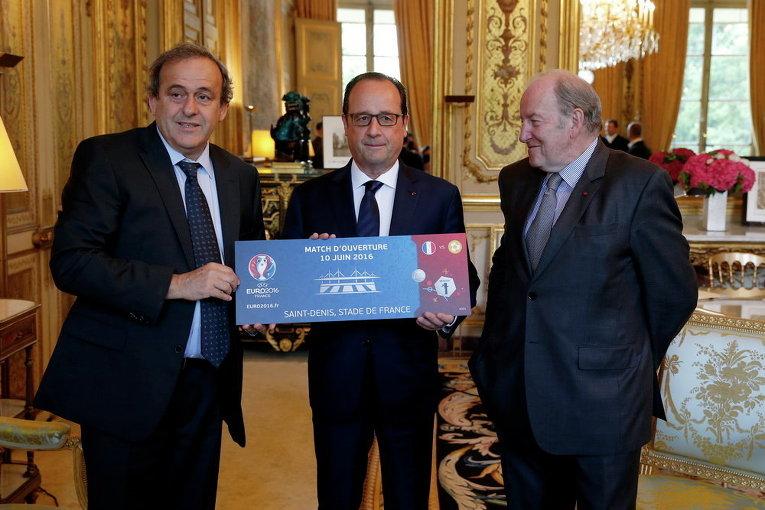 Президент УЕФА Мишель Платини и председатель УЕФА Евро-2016 Жак Ламбер дарят билет Евро-2016 президенту Франции Франсуа Олланду во время встречи в Елисейском дворце в Париже, Франция