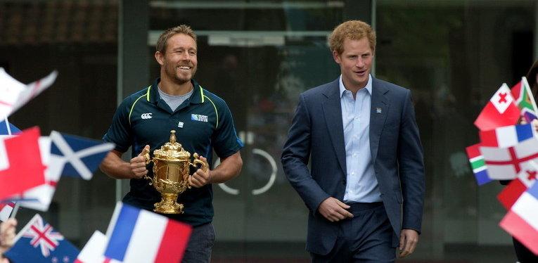 Британский принц Гарри с английским игроком в регби Джонни Уилкинсоном, который держит Кубок мира по регби