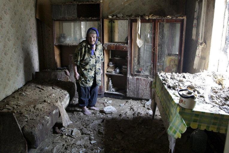 Пожилая женщина осматривает развалины дома, разрушенного обстрелами на окраине Донецка