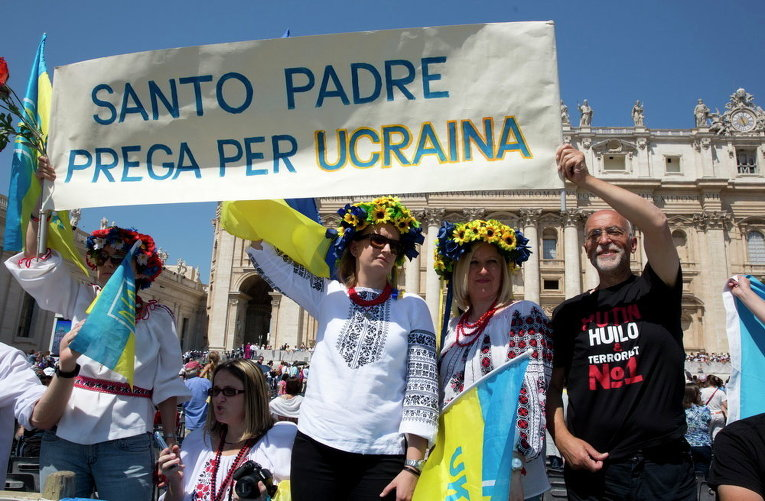 Люди держат украинские флаги и плакат с надписью Святой Отец, молись за Украину во время еженедельной общей аудиенции Папы Франциска на площади Святого Петра в Ватикане