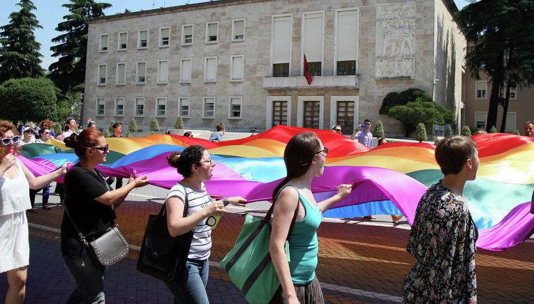 Лесбиянки, геи, бисексуалы и трансгендеры проводят марш перед главным зданием правительства в центре города Тирана