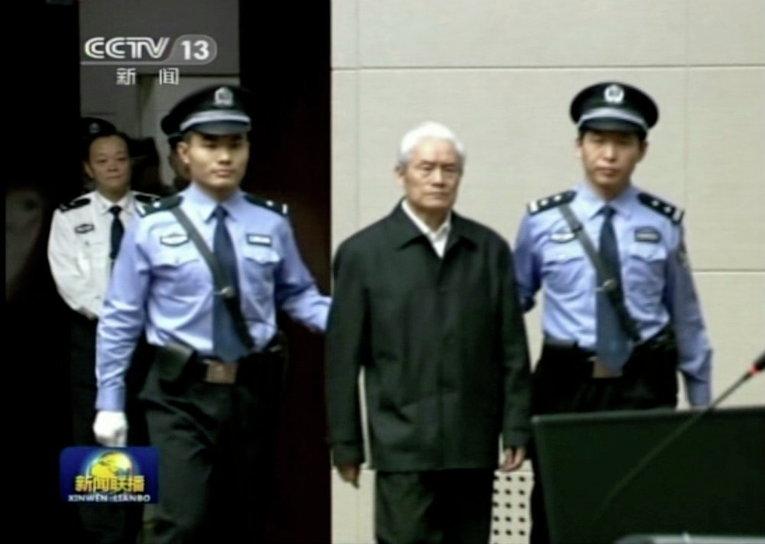 Полицейские ведут Чжоу Юнкана, бывшего члена Коммунистической партии Постоянного комитета Политбюро, отвечающего за безопасность, в зал суда в Тяньцзине, Китай