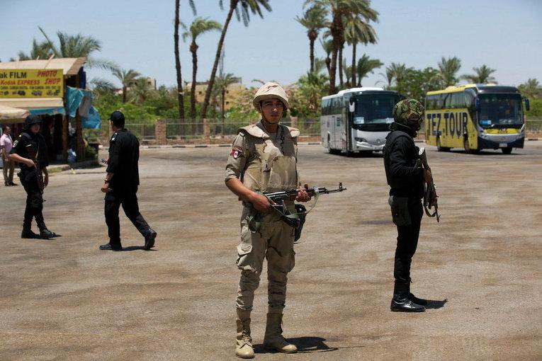 Египетские силы безопасности стоят на страже перед туристических автобусов на месте теракта возле Карнакского храма в Луксоре, Египет