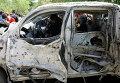 Пакистанские полицейские осматривают автомобиль, взорванный во время теракта в Пешаваре, Пакистан