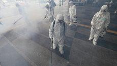 Работники в Сеуле обрабатывают антисептическим раствором улицу из-за распространения коронавируса