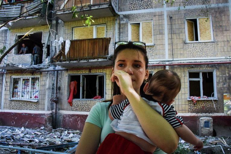 Женщина с ребенком у ее поврежденного в результате обстрелов дома в Горловке