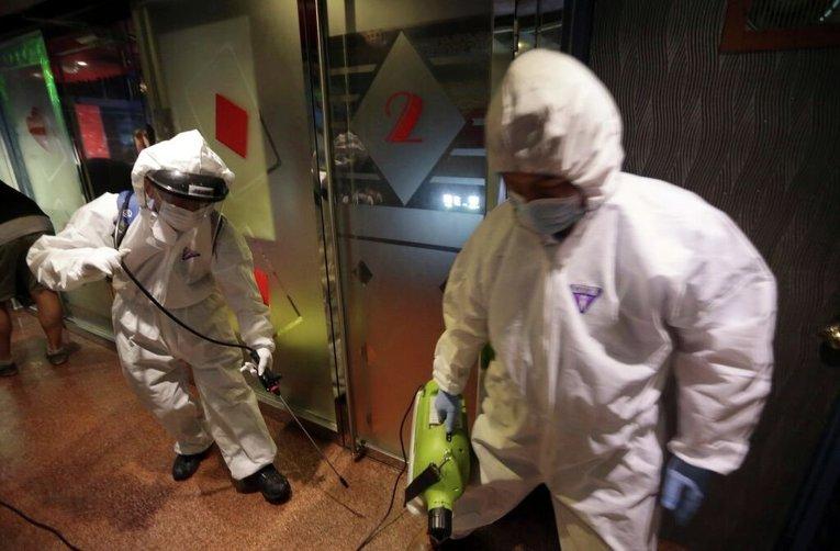 Работники дезинфицируют оборудование в качестве меры предосторожности против МЕРС в караоке-зале в Сеуле