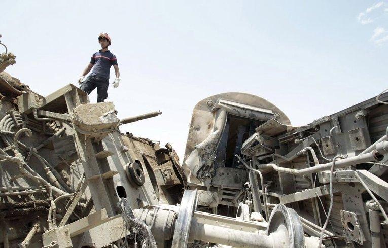 Спасатель стоит на месте столкновения пассажирского поезда и грузовика в южной части города Cфакс
