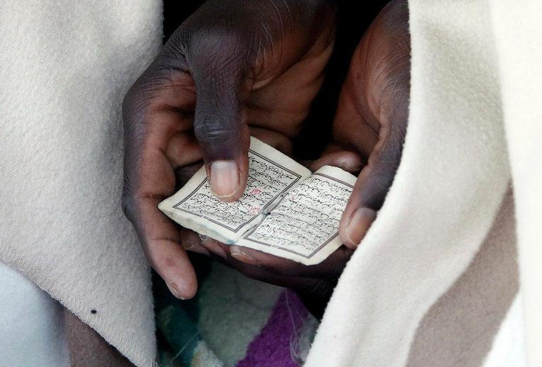 Мигрант, завернутый в одеяло, читает Коран на складах дамбы на берегу Средиземного моря между Италией и Францией.
