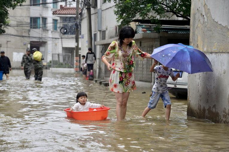 Женщина с детьми идет через затопленные улицы после сильного ливня в Чанчжоу, провинция Цзянсу, Китай
