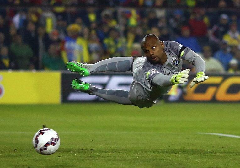 Бразильский вратарь Джефферсон ныряет за мячом во время футбольного матча против Колумбии на стадионе Monumental David Arellano в Сантьяго